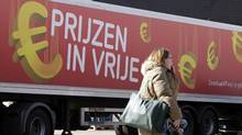 A woman walks in front of a delivery truck with the euro symbol which reads 'Prices in free fall, so much more for your money' in Brussels on Monday, March 12, 2012. (Virginia Mayo/AP)