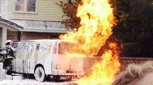 Firefighters tend to a van that burst into flames after it collided with a concrete wall Monday, Oct. 7, 2013 in Vancouver. Police said gasoline caused the explosions, not meth lab chemicals, as they had suggested earlier. (JESSICA WILSON)