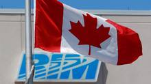 The Canadian flag flies in front of Research In Motion's company logo in Waterloo, Ont., June 29, 2012. (Dave Chidley/The Canadian Press)