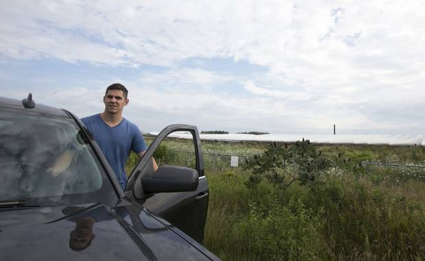 Josh Dewachter stands outside the fence at the Siemens wind turbine blade manufacturing plant in Tillsonburg, Ont.