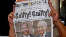 A newspaper vendor holds up a paper with a banner headline outside the federal courthouse after Enron founder Ken Lay and former CEO Jeff Skilling were convicted in Houston May 25, 2006. (TIM JOHNSON/REUTERS)