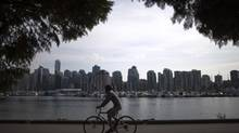 A man rides his bicycle along the seawall in Stanley Park with a backdrop of downtown Vancouver, British Columbia, Monday, September 19, 2011. (Rafal Gerszak For The Globe and Mail)