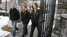 Dalhousie University women's hockey team players, from left, Miranda McMillan, Isabelle Germain and Laura Brooks, walk through the gates to campus in Halifax on Feb. 21, 2013. Veteran members of the hockey team were suspended over a hazing ritual. (Paul Darrow for The Globe and Mail)