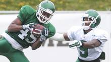 Defensive back Donnie Fletcher, left, intercepts a pass intended for running back Matt Brown during the Saskatchewan Roughriders training camp in Saskatoon, Sask., Sunday, June 1, 2014. (The Canadian Press)