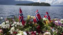 A makeshift memorial of Norwegian flags and flowers in Utvica, near Sundvollen, Norway, for those killed in a shooting spree on Utoya Island, seen in background, July 27, 2011. (JOHAN SPANNER/NYT)