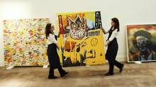 "Sotheby's employees move Jean-Michel Basquiat's Orange Sports Figure. Three of the artist's works set successive auction records this year. The artist's work has been fetching such high prices, past Takashi Murakami's ""open Your Hands Wide, Embrace Happiness!"" (L) and Cindy Sherman's ""Unititled #421"" at Sotheby's auction house in London February 1, 2012. The Basquiat is estimated to sell for up to 4 million GBP ($6.3 million) when auctioned on February 15. REUTERS/Luke MacGregor (BRITAIN - Tags: ENTERTAINMENT BUSINESS) (Luke MacGregor/Reuters)"
