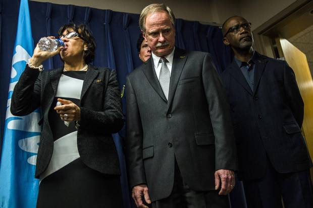 Flint Mayor Karen Weaver drinks from a bottle of water beside Keith Creagh, director of Michigan's Department of Environmental Quality, as Governor Rick Snyder fields questions from reporters on Jan. 27.