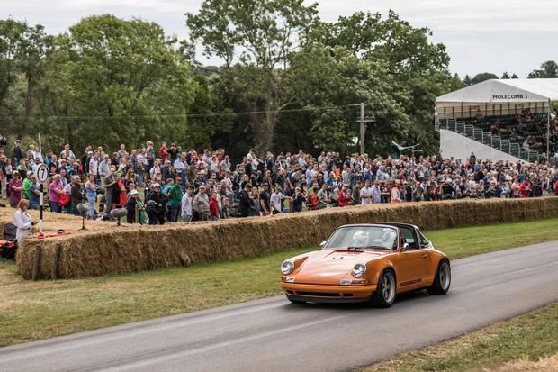 A vintage Porsche races past the Goodwood crowd.