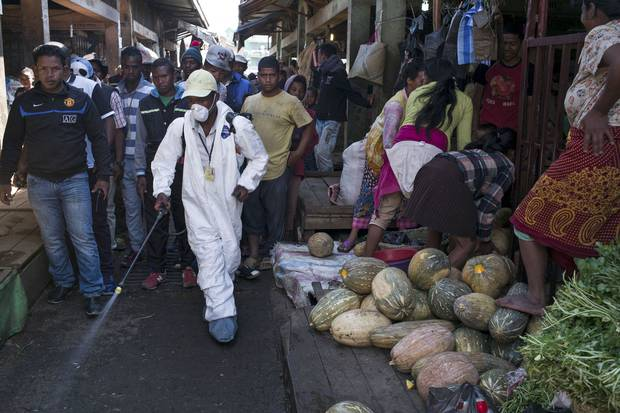Oct. 10, 2017: People stand back as a council worker sprays disinfectant to clean up a market in Tananarive, capital of Madagascar. The World Health Organization has warned that a deadly outbreak of the plague, which began in late August, is swiftly spreading in cities across the country.