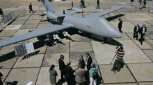 In this file photo dated Monday July 14, 2008 visitors talk and wander around a Mantis unmanned aircraft by BAE Systems PLC during a presentation at the opening day of the Farnborough aerospace show, in Farnborough, England. (LEFTERIS PITARAKIS/ASSOCIATED PRESS)