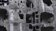Men stand in a damaged building in the Duma neighbourhood of Damascus March 14, 2014. (BASSAM KHABIEH/REUTERS)