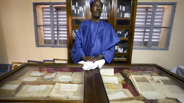 In this photo taken Tuesday, Mar. 16, 2004, an unidentified worker looks after some of the 20,000 preserved ancient Islamic manuscripts which rest in air-conditioned rooms at the Ahmed Baba Institute in Timbuktu, Mali. (Ben Curtis/AP)