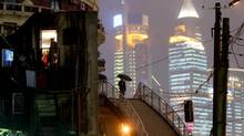 A Chinese woman (with umbrella) walks in between the new and old districts of Shanghai, October 31, 2002. (GUANG NIU/REUTERS)