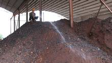 A worker hoses down ore at a plant in Huebei, China. The reason behind recent cancellations of iron ore and thermal coal contracts by Chinese buyers is a hotly debated topic in the physical commodities market. (Andy Hoffman/Andy Hoffman/The Globe and Mail)