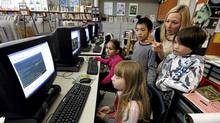Jessica Shanani, 8, Mia Miric, 8, Hao Chen Yu, 9, teacher Kathleen Tilly and Aidan Isaac Ley, 8, discuss a video in the library at Eglinton Public School in Toronto. (Deborah Baic/Deborah Baic/The Globe and Mail)
