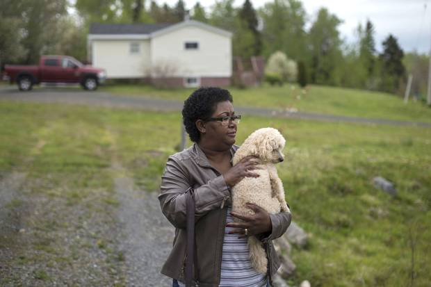 Shanna Desmond's mother, Thelma Borden, holds Penny G, her granddaughter Aaliyah's dog, outside her home where the killings took place.