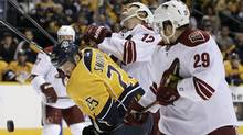 Nashville Predators centre Jerred Smithson (25) battles for the puck with Phoenix Coyotes left wing Paul Bissonnette (12) and centre Petteri Nokelainen (29) in the second period of an NHL hockey game on Oct. 13 in Nashville. (Mark Humphrey)