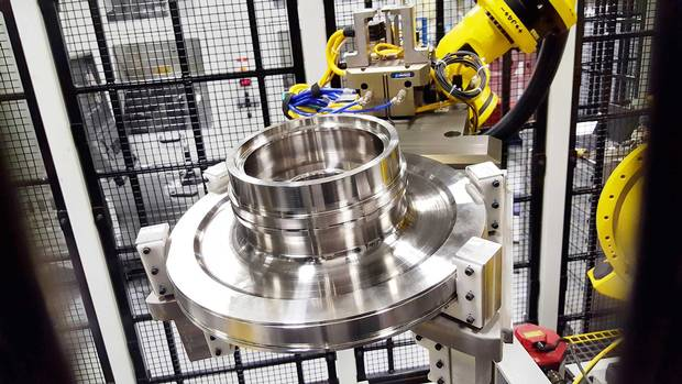 Inside a wire cage, a robot readies material to craft an engine turbine component. It looks like an ornate disc brake you might find in your car—but costs as much as an entire vehicle.