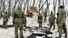 Members of the Princess Patricia's Canadian Light Infantry wait for sandbags to be unloaded as they shore up up a dike along an Assiniboine River near Poplar Point, Manitoba, May 12, 2011. (Fred Greenslade/Reuters/Fred Greenslade/Reuters)