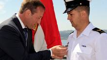 Leading Seaman Mathieu Blais receives a War of 1812 memorial pin from Defence Minister Peter MacKay. (Corporal Charles Stephen)
