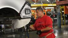 A worker builds automobiles on a General Motors assembly line at the company's plant in Oshawa, Ont. (Kevin Van Paassen/The Globe and Mail)