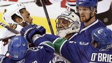Chicago Blackhawks right wing Dustin Byfuglien crashes into Vancouver Canucks goalie Roberto Luongo as Alex Burrows, Shane O'Brien and Henrik Sedin come to assist in the third period during Game 3 of their NHL Western Conference semi-final hockey game in Vancouver, British Columbia May 5, 2010. (ANDY CLARK/REUTERS)
