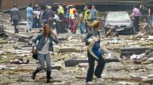Two women are seen leaving as rescue workers arrive to evacuate the injured at the site of a powerful explosion that rocked central Oslo July 22, 2011. (Thomas Winje/Reuters/Thomas Winje/Reuters)
