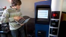 John Russell, co-founder of Robocoin, works out the kinks of what is being billed as the world's first Bitcoin ATM at a coffee shop in Vancouver, Oct. 29, 2013. (JONATHAN HAYWARD/THE CANADIAN PRESS)