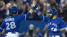 Toronto Blue Jays right fielder Jose Bautista (19), right, celebrates his 8th inning home run at home plate with teammate Colby Rasmus (28). TheToronto Blue Jays defeated the New York Yankees 4-0 during AL baseball action in Toronto on Saturday, April 5, 2014. (CP)