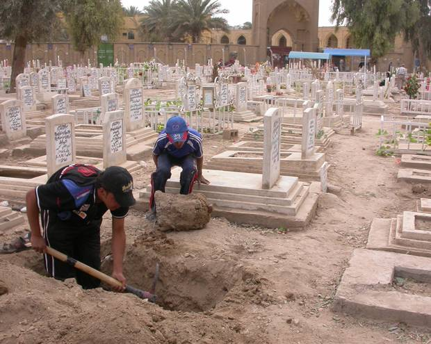 Residents of a Baghdad neighbourhood dig a fresh plot in the graveyard in 2008.