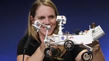Jennifer Trosper, Mars Science Laboratory mission manager, holds a model of NASA's Mars science rover Curiosity as she speaks during a news conference at NASA's Jet Propulsion Lab in Pasadena, Calif., on Aug. 6, 2012. (FRED PROUSER/REUTERS)
