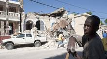 A man takes a break from clearing rubble from a damaged house in Jacmel, Haiti. (Adrian Wyld)