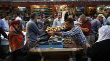 Iraqi Kurdish residents buy groceries ahead of the Muslim fasting month of Ramadan at a market in central Arbil, in Iraq's Kurdistan region in the June 28, 2014, photo. (AHMED JADALLAH/REUTERS)