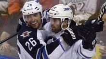 Winnipeg Jets' Blake Wheeler (26) and Andrew Ladd celebrate after Ladd scored in the third period of an NHL hockey game against the Florida Panthers in Sunrise, Fla., Tuesday, April 3, 2012. (Associated Press)