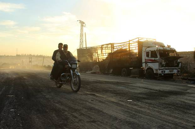 Men drive a motorcycle near a damaged aid truck after an airstrike in western Aleppo.