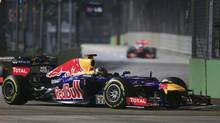 Red Bull Formula One driver Sebastian Vettel of Germany drives ahead of McLaren Formula One driver Jenson Button of Britain during the Singapore F1 Grand Prix at the Marina Bay street circuit in Singapore September 23, 2012. (PABLO SANCHEZ/REUTERS)