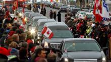 Residents line the road as five hearses carrying the remains of four fallen Canadian soldiers and Michelle Lang, a Canwest journalist from Calgary, embedded with the Canadian Forces in Afghanistan, drive past during a repatriation ceremony at Canadian Forces Base Trenton, Sunday. (MIKE CASSESE/MIKE CASSESE/REUTERS)
