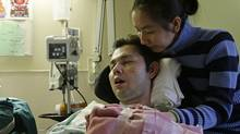 Michael Phan is comforted by his wife, Le Phuong, at Royal Columbian Hospital in New Westminster, B.C., on Thursday October 16, 2008. (Darryl Dyck for The Globe and Mail/Darryl Dyck for The Globe and Mail)