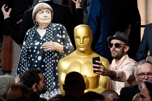 JR, right, takes a selfie with an Oscar statue and a cardboard cutout of Agnes Varda.