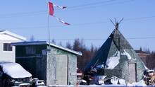 The remains of a Canadian flag can be seen flying over a building in Attawapiskat, Ont., on November 29, 2011. (Adrian Wyld/THE CANADIAN PRESS)