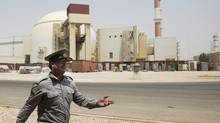 In this Saturday, Aug. 21, 2010, file photo, an Iranian security directs media at the Bushehr nuclear power plant, with the reactor building seen in the background, just outside the southern city of Bushehr, Iran. The U.S. has plans in place to attack Iran if necessary to prevent it from developing nuclear weapons, Washington's envoy to Israel said, days ahead of a crucial round of nuclear talks with Tehran. (Vahid Salemi/AP)
