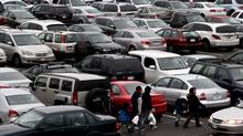 Shoppers walk past a sea of cars that fill a parking lot at Oakridge Centre mall in Vancouver. (DARRYL DYCK/DARRYL DYCK FOR THE GLOBE AND MAIL)