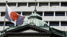 A Japanese flag flutters atop the Bank of Japan headquarters building in Tokyo in this October 26, 2011 file photograph. (YURIKO NAKAO/REUTERS)