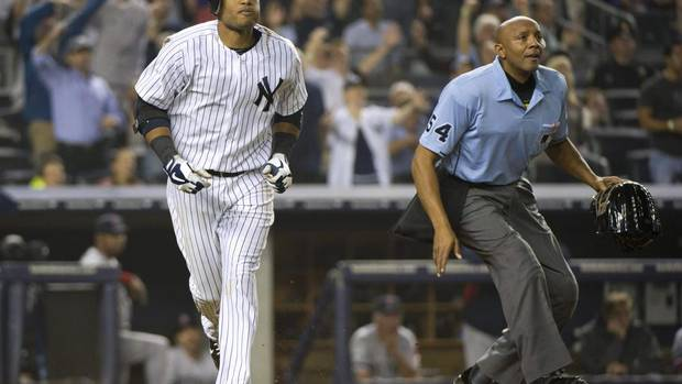 New York Yankees batter Robinson Cano and home plate umpire CB Bucknor (R) watch the ball after he hit a two-run home run, his second of the game, against the Boston Red Sox in the fifth inning of their American League game at Yankee Stadium in New York, October 3, 2012. (RAY STUBBLEBINE/REUTERS)