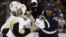 Pittsburgh Penguins' Deryk Engelland, left, and St. Louis Blues' Ryan Reaves fight during the first period of an NHL hockey game on Saturday, Nov. 9, 2013, in St. Louis. (Jeff Roberson/AP)