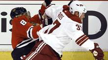 Chicago Blackhawks' Marian Hossa (L) is checked by Phoenix Coyotes' Raffi Torres during Game 3 of their NHL Western Conference quarter-final playoff hockey game in Chicago. (JIM YOUNG/Reuters)