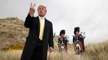 Donald Trump humorously gives a two fingered gesture to the media on the Menie Estate, where his controversial luxury golf resort will be built. The coastal resort in Balmedie, Aberdeenshire, will have two golf courses, a 450-bedroom hotel, 950 holiday apartments and 500 residential homes. (Andrew Milligan/PA Wire/Press Association Images)