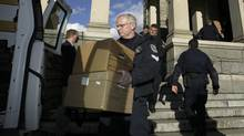 Members of Victoria Police assist the RCMP in moving seized evidence during a raid on the offices of the Minister of Finance Gary Collins and of the Minister of Transportation Judith Reid at the B.C. Legislature in Victoria on Dec. 28, 2003. Police were investigating staff who work in the ministers' offices. (Bruce Stotesbury/The Canadian Press)
