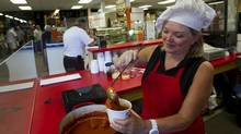 Vendor Cindy Sellner of Just'a Meatballs works at her indoor stall. (Kevin Van Paassen/The Globe and Mail)