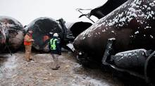 National Transporation and Safety Board (NTSB) member Robert Sumwalt (R) views damaged rail cars at the scene of the BNSF train accident in Casselton, North Dakota January 1, 2014 in this handout provided by NTSB. (NTSB/REUTERS)